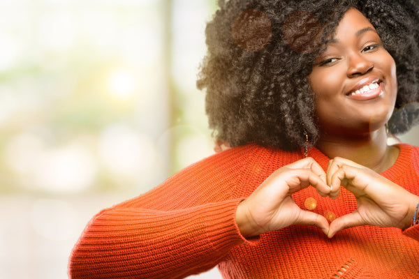 is olive oil good for you what are the benefits of olive oil woman wearing orange sweater making a heart with her hands smiling bright blurred background
