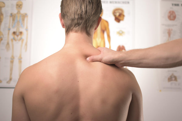 view of upper back of male patient with doctor's hand on upper shoulder