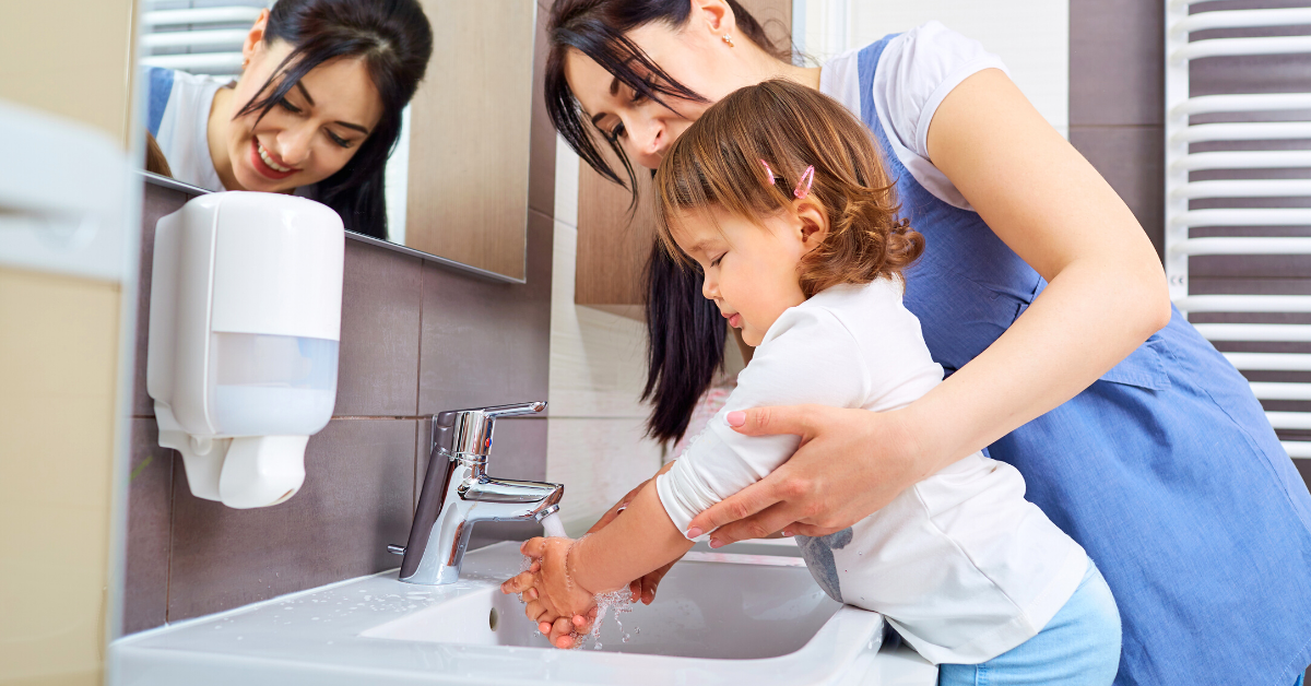 mom helping daughter wash her hands over the sink