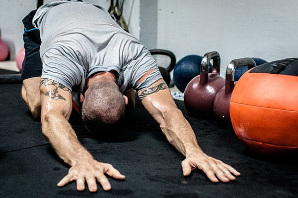 muscle cramps 101 causes and natural remedies man at the gym wearing gray and black stretching his back before exercise