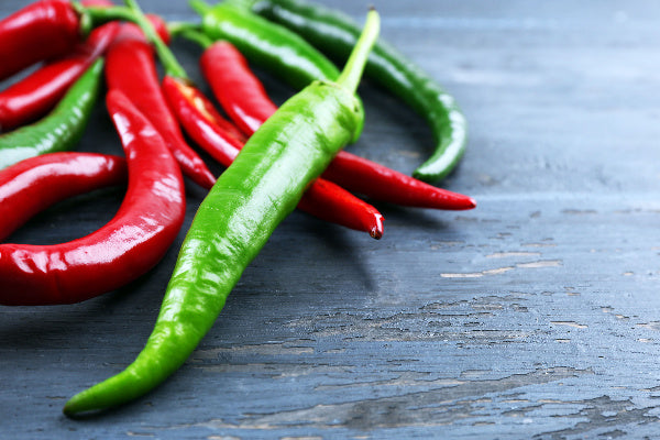 postherpetic neuralgia symptoms causes and natural treatment for postherpetic neuralgia red and green peppers sitting on a black wood table sources of capsaicin for postherpectic neuralgia