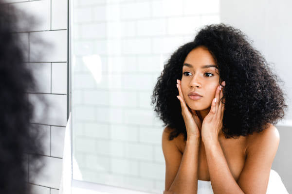 Woman moisturizing skin while looking in mirror