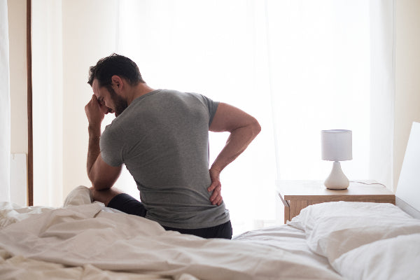 sciatic nerve pain relief natural remedies man holding his back with sciatic nerve pain sitting on a bed