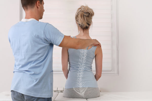 scoliosis back pain how to relieve it woman getting her back checked out at doctors office diagnosis white room