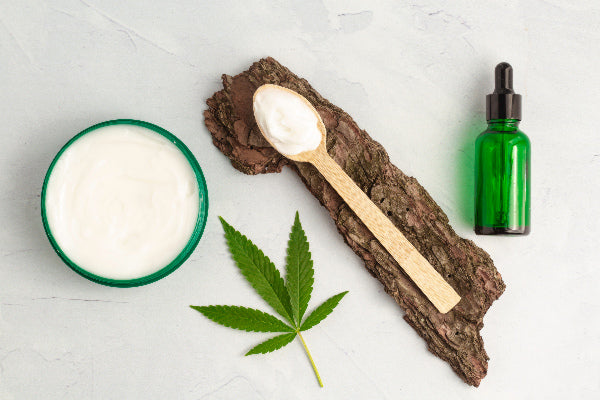 si joint dysfunction causes symptoms and si joint pain natural remedies cbd oil and cream cbd cream in wooden spoon on bark marijuana leaf on white counter background