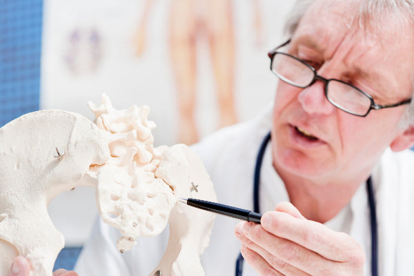 si joint dysfunction causes symptoms and si joint pain natural remedies doctor wearing glasses using a pen to point to the si sacroiliac joint in doctors office patient education