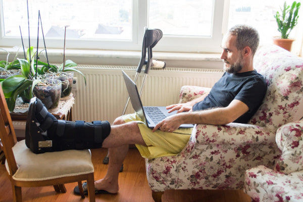 tendonitis vs tendinosis what is the difference man sitting on flower print arm chair with foot elevated in a boot for tendonitis working on a laptop crutches beside him
