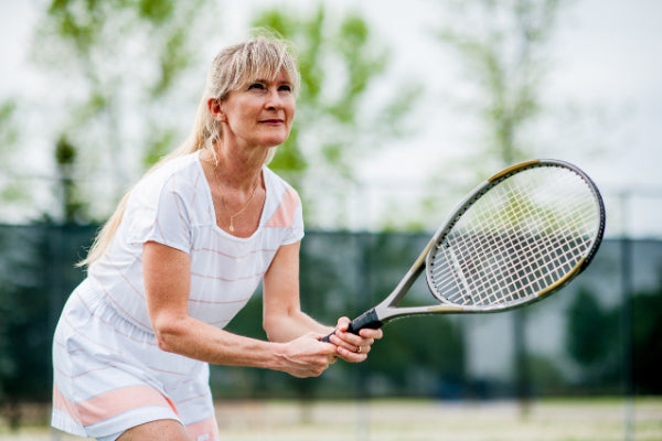 tendonitis vs tendinosis what is the difference middle aged woman wearing white striped jumper in a tennis stance with a racket in her hand
