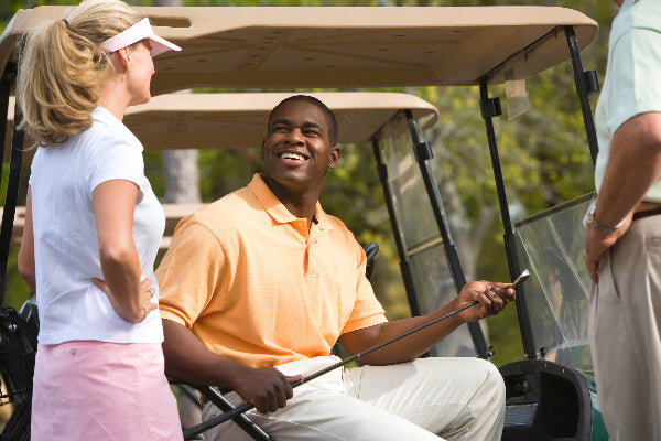 tennis elbow vs golfers elbow natural remedies for elbow pain from tennis golfers elbow man smiling at woman sitting an a golf cart elbow pain free