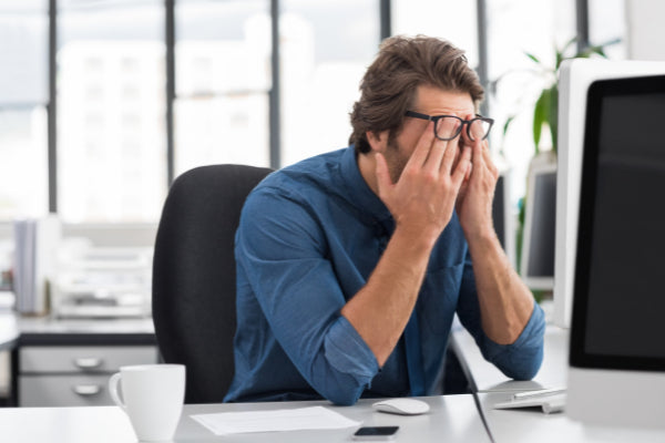 the benefits of an essential oil diffuser man sitting at desk stressed work rubbing his eyes
