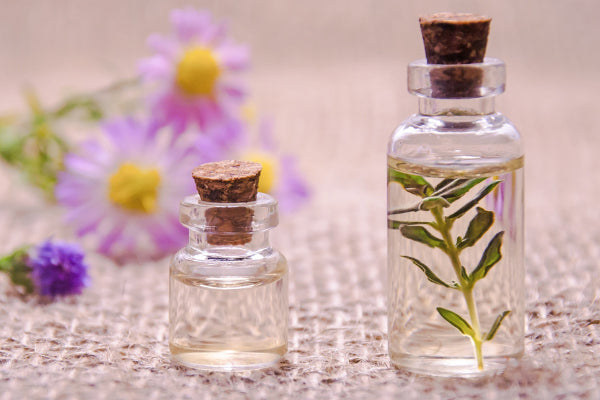 the best natural remedies for anxiety clear bottles with oils and with purple flowers in the background on burlap