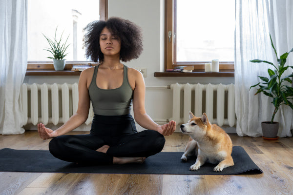 the best natural remedies for anxiety woman meditating for anxiety on black yoga matt with dog