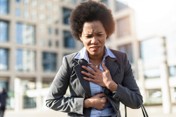 the relationship between anxiety and pain can anxiety cause chest pain person holding chest in front of business