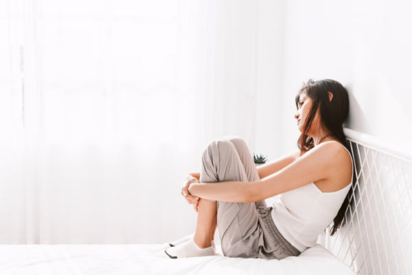 the relationship between anxiety and pain person sitting on white bed looking down stressed anxious white background