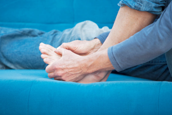 top 10 causes of joint pain person sitting on blue couch wearing blue holding toes in pain from gout