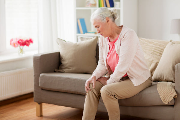 top 10 causes of joint pain woman sitting on the couch in pain holding her knee