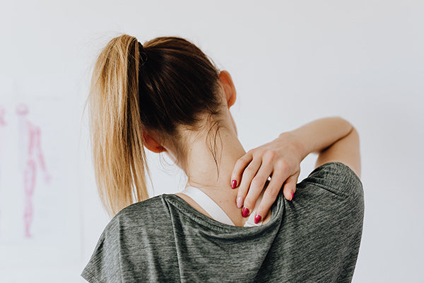 using dmso for muscle pain relief woman person touching the back of her neck from muscle pain gray shirt in the doctors office blurred background
