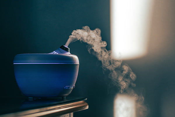 vetiver essential oil benefits and uses blue diffuser on table close up with blurred background