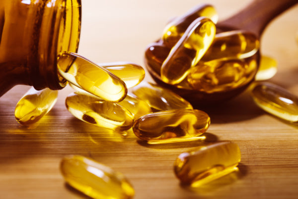 what are the benefits of omega 3 how much omega 3 per day should i take sources of omega 3 foods with omega 3 supplements spilling out of an amber bottle wooden spoon wood table