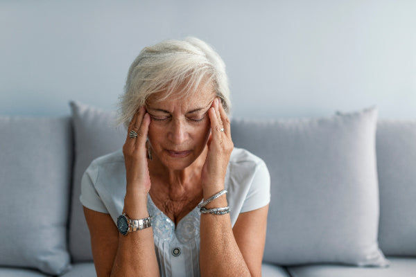 what are the health benefits of magnesium supplements side effects and recommended dosage woman holding temples due to migraine headache