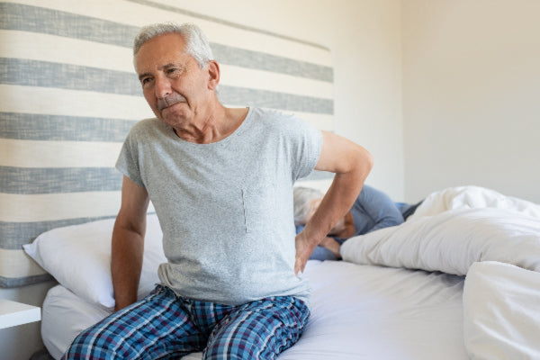 what causes back pain what are the different types of back pain natural remedies that can help elderly man getting out of bed with back pain wearing pjs