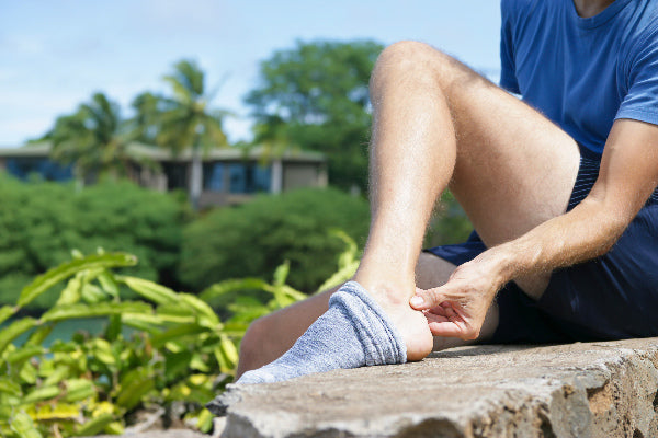 what is achilles tendinosis achilles tendinosis symptoms causes natural treatment of achilles tendinosis man in blue shirt navy shorts holding ankle sitting on stone barrier