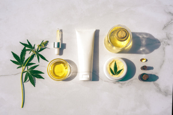 what is ankylosing spondylitis ankylosing spondylitis symptoms causes natural treatments cbd cream oil supplement sitting on marble table with marijuana leaf above view