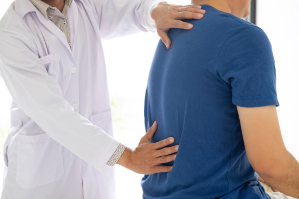 what is ankylosing spondylitis ankylosing spondylitis symptoms causes natural treatments doctor feeling the lower back of male patient in blue t shirt due to pain in office