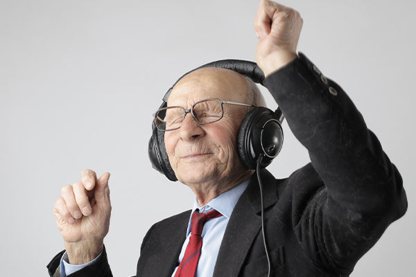what is bergamot bergamot essential oil benefits uses elderly man with over the ear headphones on with eyes closed enjoying the music arms up white background