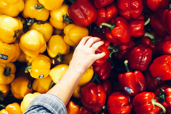 what is capsaicin the benefits of capsaicin the foods with capsaicin pile of separated red and yellow bell peppers woman wearing denim grabbing one