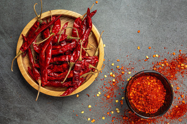 what is capsaicin the benefits of capsaicin the foods with capsaicin red chili peppers dried and ground up wooden plate bowl on table