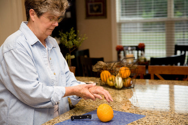 what is guillain barre syndrome cause natural treatment options available that may help elderly woman at the kitchen counter cutting an orange holding her wrist in pain wearing blue denimn layered shirt