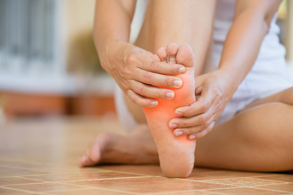 what is metatarsalgia metatarsalgia symptoms causes natural remedies woman wearing white sitting on tile floor holding the ball of her foot in pain red pain orb