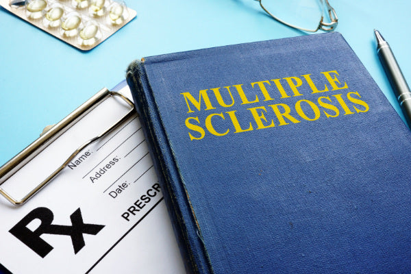 what is multiple sclerosis blue book with ms on the front in yellow sitting on rx pad close up