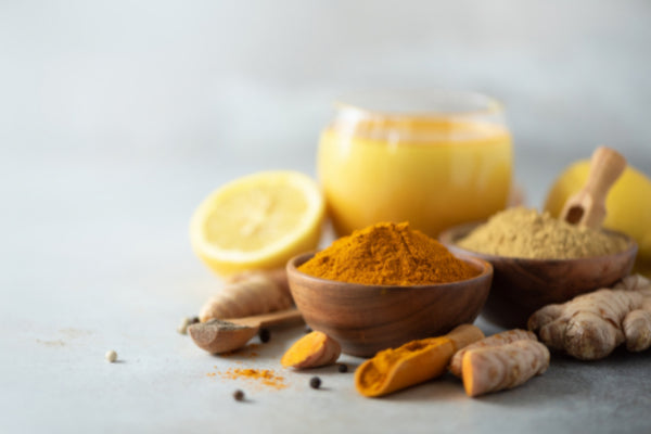 what is multiple sclerosis turmeric powder in wooden bowl next to root on white table