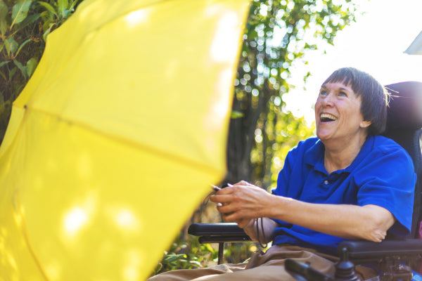 what is multiple sclerosis woman wearing blue shirt in wheelchair holding yellow umbrella smiling
