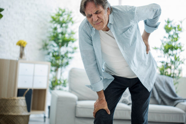 what is osteoarthritis symptoms causes natural remedies man in blue shirt bending over with lower back hip pain