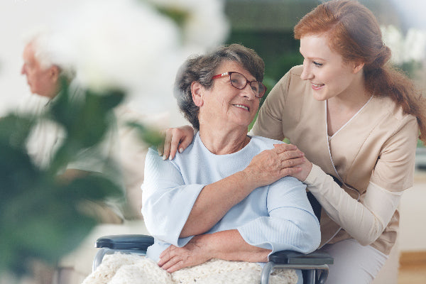 what is osteoporosis the causes symptoms of osteoporosis and natural remedies for osteoporosis woman with short hair wearing blue shirt sitting in a wheelchair with a blanket in her lap nurse aid touching her shoulder