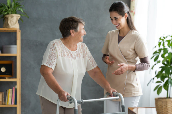 what is parkinsons disease nurse helping a woman using a walking both smiling