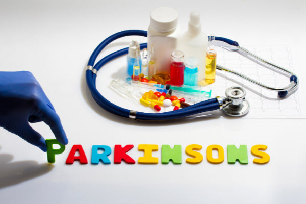 what is parkinsons disease spelled out in different color letters next to pill bottles stethoscope