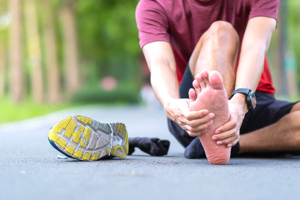 what is plantar fasciitis the causes of plantar fasciitis symptoms natural remedies for plantar fasciitis essential oils man in red shirt black shorts sitting on the ground holding foot in pain