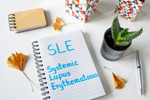 what is systemic lupus erythematosus symptoms of systemic lupus erythematosus and natural remedies notebook sitting on white desk with blue highlighter with cactus flowers pen on desk