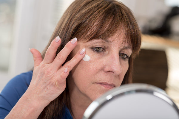 what is trigeminal neuralgia causes symptoms treatment brunette woman looking in a mirror putting pain relieving topical cream on her face wearing a blue shirt