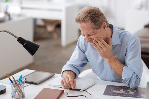 what is trigeminal neuralgia causes symptoms treatment man holding his face because of nerve pain sitting at a desk wearing blue collared shirt