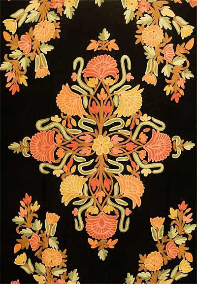 Colorful shawl embroidered with flowers in shades of red, peach, maize, green and tan.