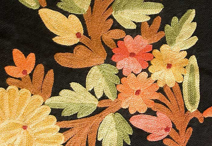 Colorful embroidered flowers in shades of red, peach, maize, green and tan on a black wool shawl.