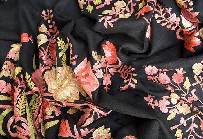 Pink flowers embroidered on a black wool shawl.