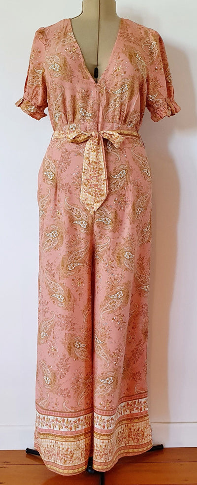 V neck jumpsuit in a peachy/paisley print,100% rayon fabric with short sleeves / elastic frill hem, fabric belt, long centre back zip, side pockets, waist band with side tabs, and fuller legs with a border print
