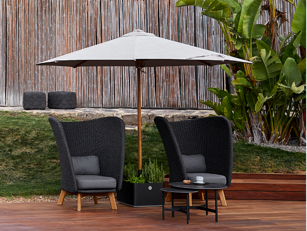 Two modern and unique lounge chairs with a Cane-line parasol