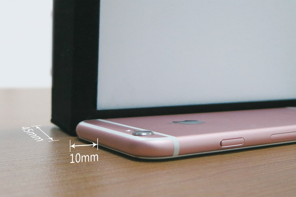 Comparison showing thickness of Nero thin bezel home theatre projector screen compared to an iPhone